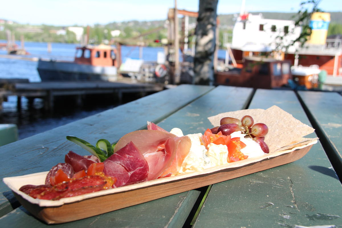 Tallerken formet som stokkebåten med spekemat, potetsalat, druer og flatbrød.