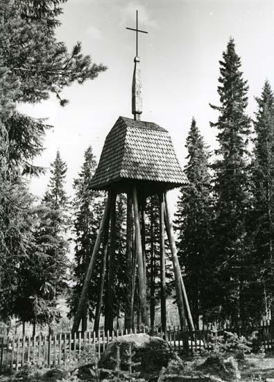 En klockstapel med tak av stavspån i mansardstil och ett krönande kors på toppen. Stapeln bärs upp av timmerbaklar och omges av barrträd samt ett staket.