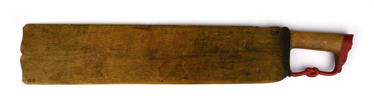 Skäktkniv av trä. På ena sidan av bladet finns blomsterornering i rött, vitt och grönt samt med bläck skrivna verser. Den andra sidan är omålad. På handtagets nederdel finns en snidad knut.
