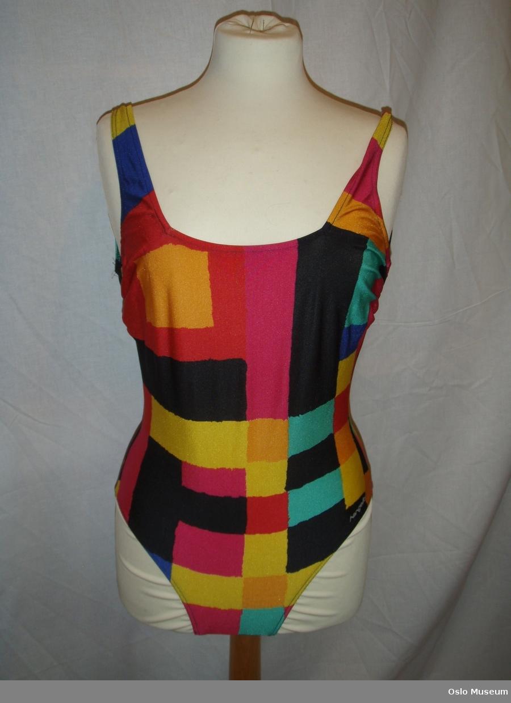 Badedrakt i størrelse 42 med geometrisk mønster i mange ulike farger. Rettskåret bryst- og rygglinning. Varemerke er festet på hoftelinning.