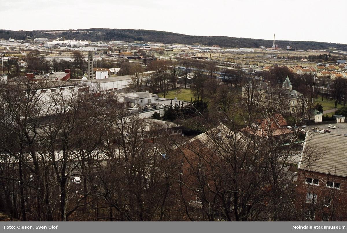Vy från Störtfjället mot sydväst. Närmast till vänster ses industribyggnader tillhörande pappersbruket Papyrus. Till höger ses Villa Papyrus och Papyrusparken. I fonden ses bland annat bebyggelse i Åbro industriområde samt Riskullaverket. Mölndal i april 1994.