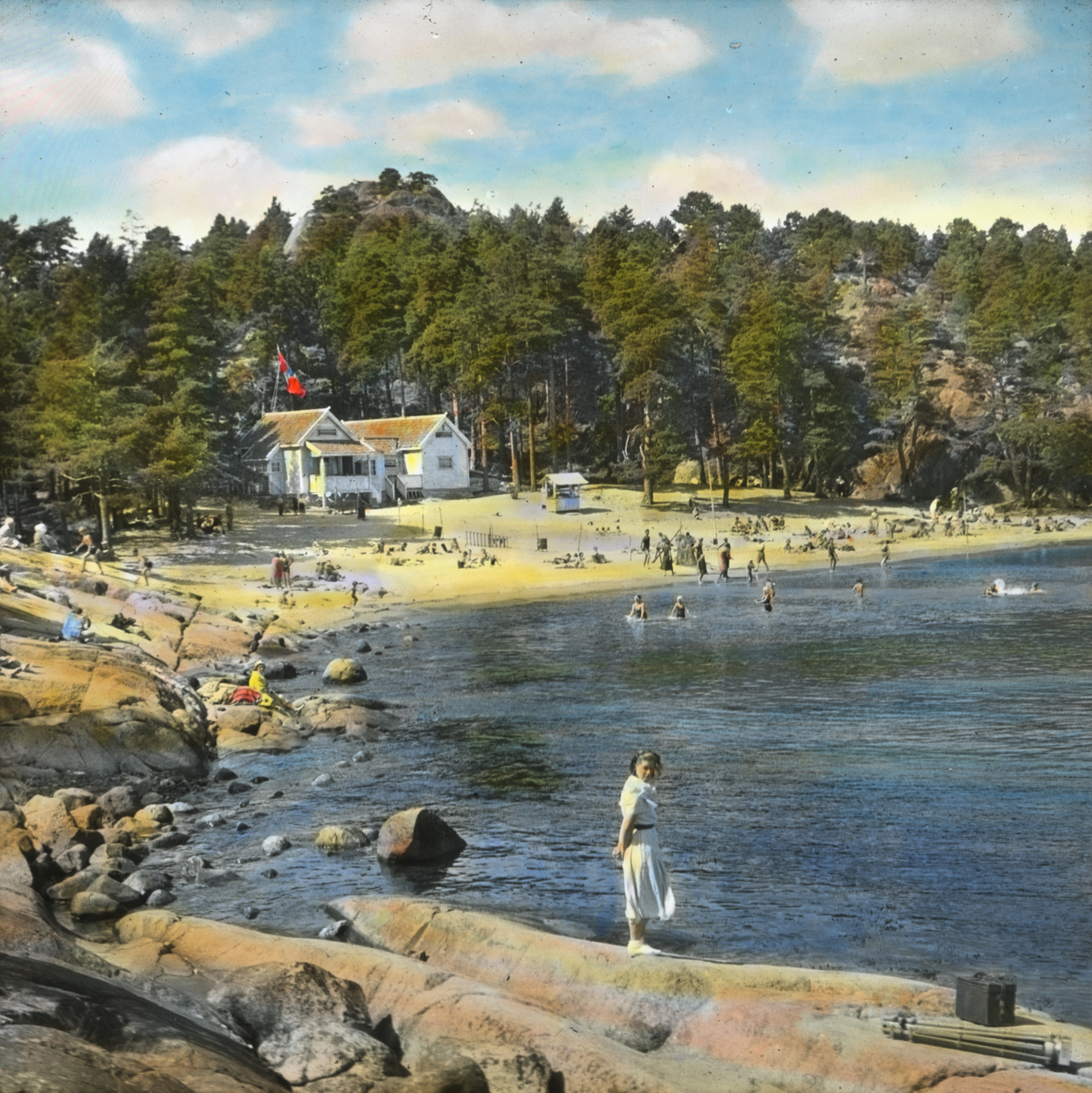 Håndkolorert dias. På bildet ser vi badende mennesker på Storesand strand i Grimstad. I bakgrunnen ser man skog og to hvite hus. En ung kvinne står på svaberget i forgrunnen.