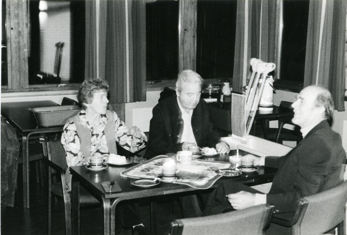 En kvinne og to menn sitter og drikker kaffe ved et bord.