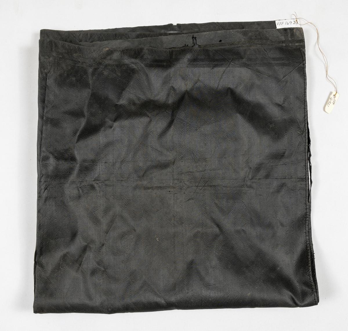 Tørkle i svart silketaft. Falda for hand i to sider, jarekant i dei to andre.