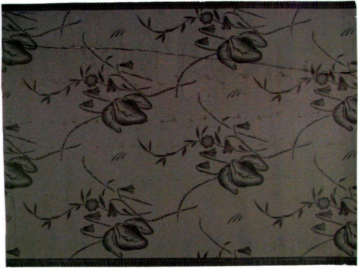 Blomma och blad i diagonalupprepning. Tryck i beigegrått på ett brunt genomfärgat papper.