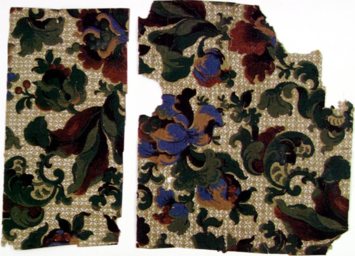 Ytfyllande fantasifullt blommönster i blått samt i flera gröna och bruna nyanser över en bakgrund med ett litet vitt mönster. Beige genomfärgat papper. Övertryck med ett svart randmönster.