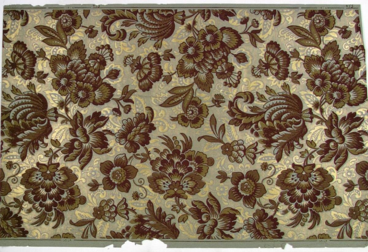 Ett fantasifullt blommönster i brunt samt i två olivgröna nyanser. Bakgrunden dekorerad med ett sgrafferat mönster i guld. Grågrönt genomfärgat papper.