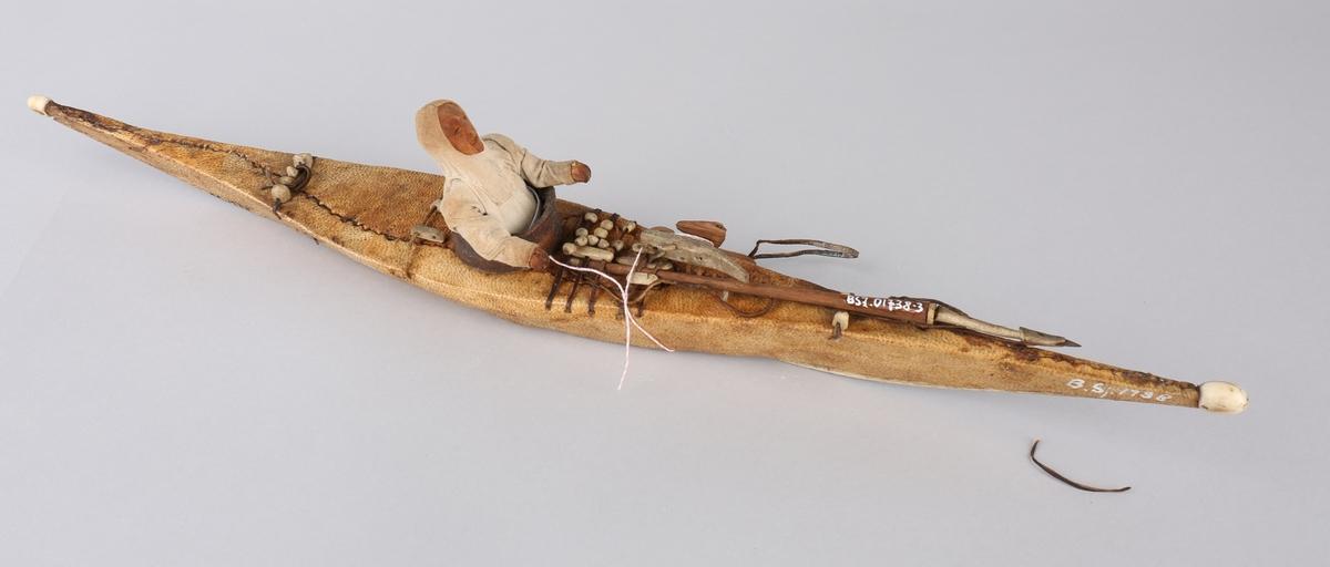 Kajakkmodell med figur og fangstredskap ombord. Ekte eskimoarbeid