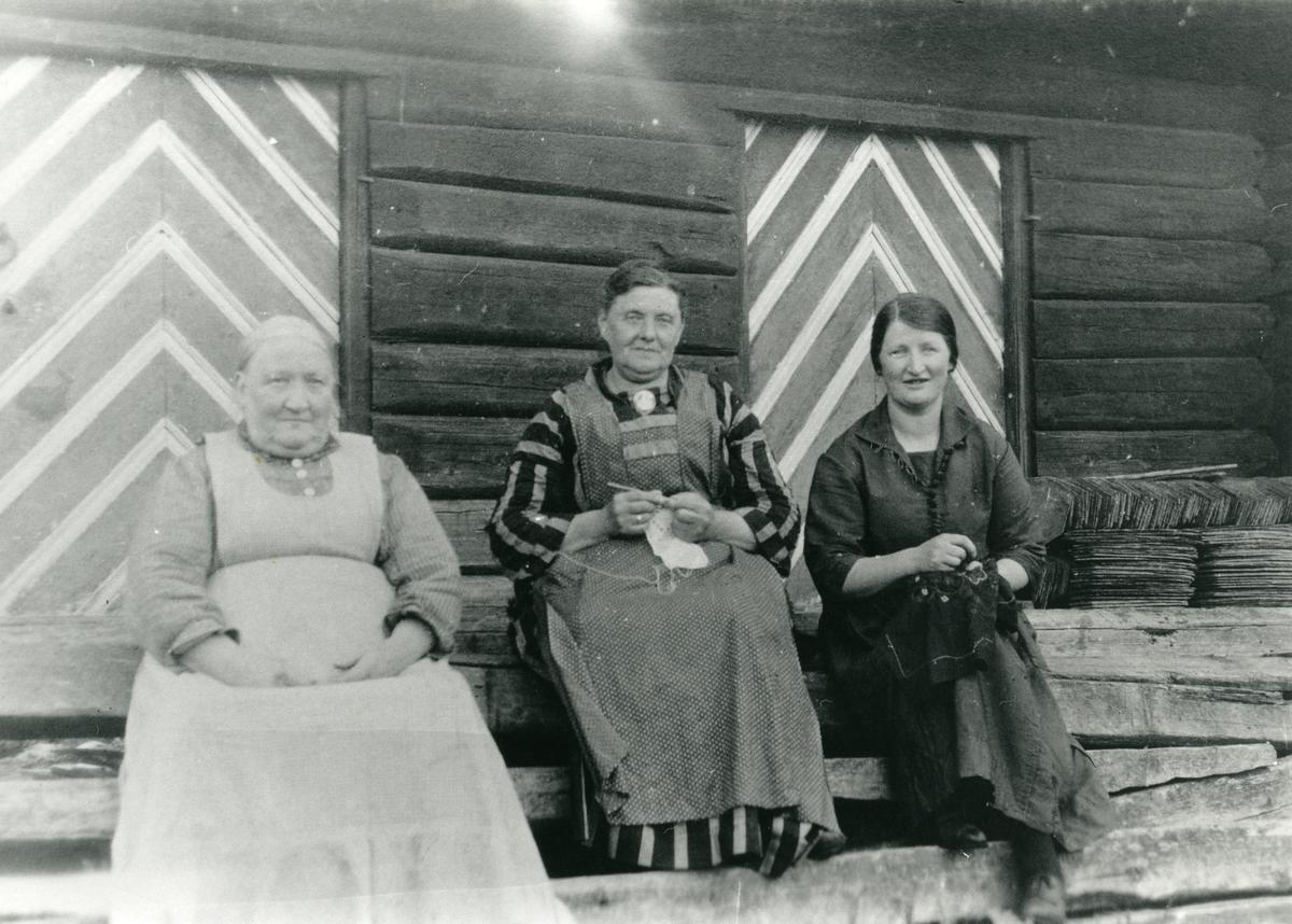 3 kvinner på trappa utenfor en tømmerbygning (stabbur?). En hekler og en broderer.