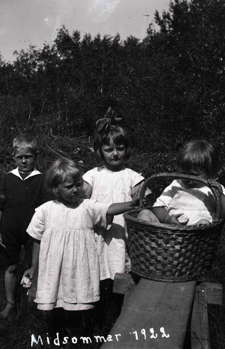 Barn varav en flicka i en korg på en träbänk.