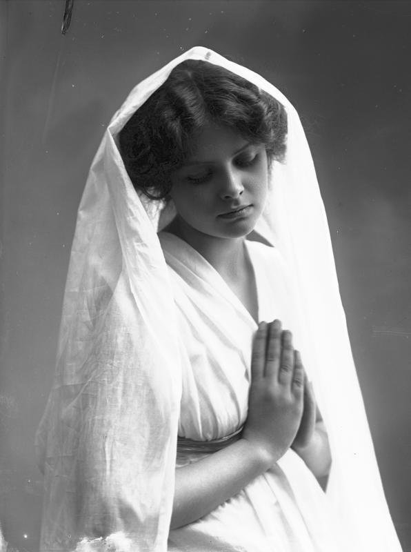 Studioportrett av kvinne i kostyme - hvit kjortel og hvitt slør, som holder hendene foldet. 1908.
