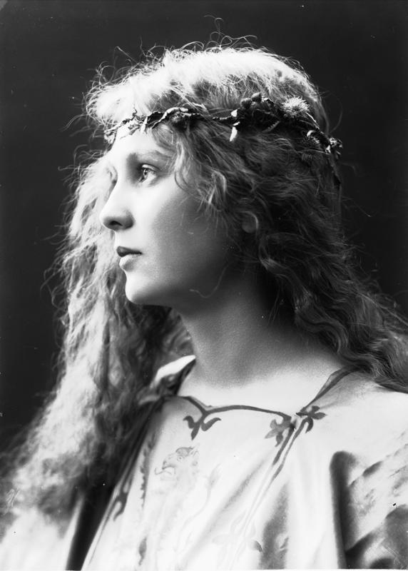Studioportrett av kvinne i kostyme og utslått hår - overdel med riksvåpen og blomsterkrans i håret. 1908.