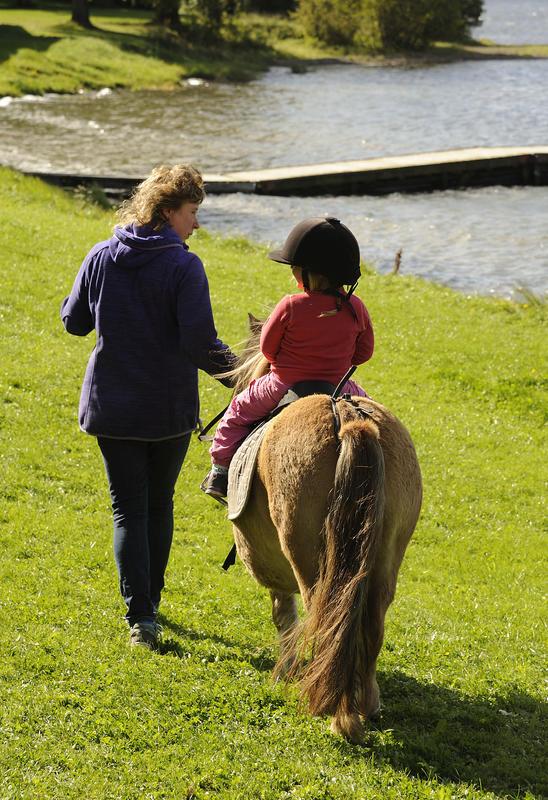 Barn med hjelm rir på en liten, brun ponny. Voksen dame går ved siden av og leier hesten.