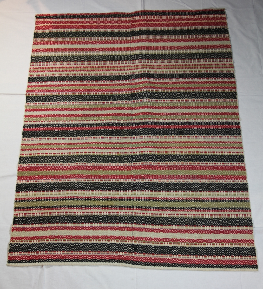 Teppe laget i bomull og ull. Bunnrenning av hvit bomull med mønstre ved islett av ull i forskjellige farger, og forskjellig slags bragveving. Tverrstriper i rødt, sort, mosegrønt, hvitt og fiolett. Stripene skifter uten noe bestemt system. To stykker sydd sammen ved midtsøm.