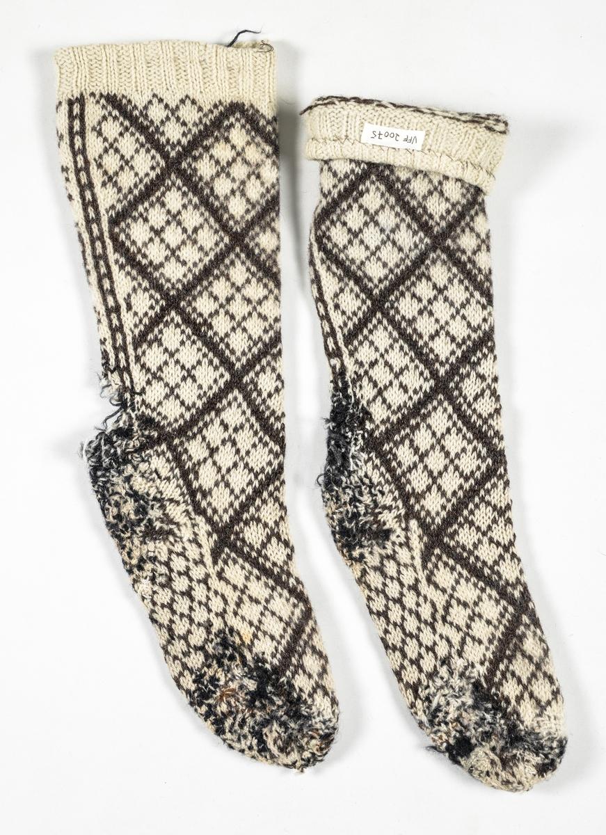Strømpe, A og B, heimestrikka strømpe i kvit og sauesvart ullgarn. Mønster med åttebladrose. Stoppa  mange plassar i foten og i hælen. Hælen har hol i stoppinga.