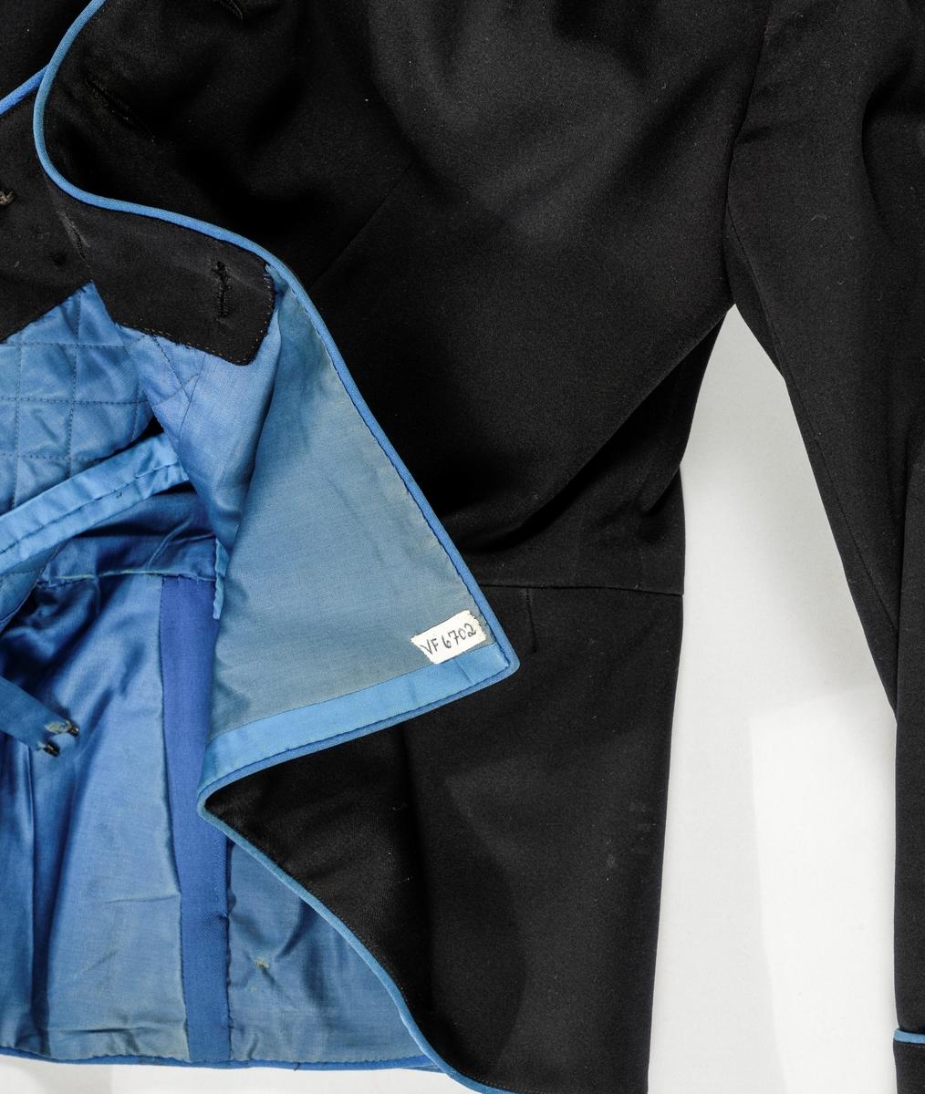 Uniformsjakke i svart klede med blåe tittekantar ved opningen framme på båe sider, langs kanten nede, rundt splitten midt bak og rundt mansjettane. Nederst påsett ei kappe. Blå ståkrage kanta med sølvband. Ei stjerne på kvar side av kragen. Åtte knappar og knappehol. Splitt i ryggen med 6 knappar. Bakovertrekte skuldersaumar, og svinga sidesaumar i ryggen. Todelt erme, mansjett med eit blått tøystykke og tre knappar på kvart erme. Fóra med blått blankt satengvove bomullstøy, vattert på framstykke ned til livet. Ei innerlomme. Spensel med hekte og krok for å halda jakka saman.