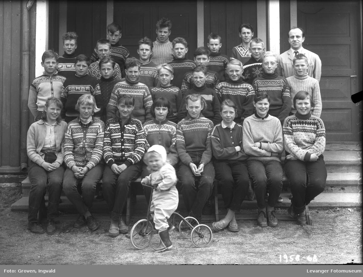 Skolebilde fra folkeskole Skole ikke kjent. med et småbarn på trehjulsykkel.