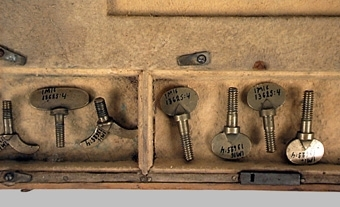"""Enl liggare: """" Avvägningsinstrumentlåda, trälåda, klädd invändigt med sämskskinn. Kvar 2 instrument och 8 vingskruvare. Synes tillhört jägmästare A. Aspengren, Mariestad."""""""