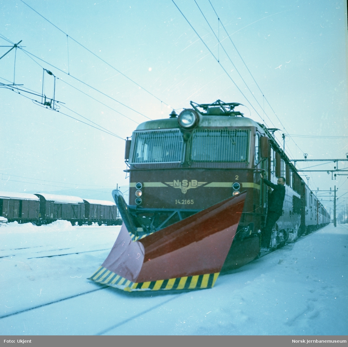 Elektrisk lokomotiv El 14 2165 med stor frontplog foran persontog på Bergensbanen
