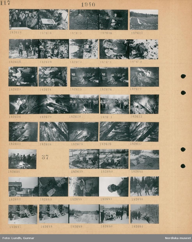 """Motiv: (ingen anteckning) ; En kvinnor och män står kring en karta, en kvinna håller en överdimensionerad kompass, en skylt vid en myrstack """"Söder"""", landskapsvy med en åker och skog, kvinnor och män vandrar i naturen, en ryggsäck, människor står kring en öppen eld, närbild av brinnande vedträn.  Motiv: (ingen anteckning) ; Två män i uniform sitter med radioutrustning på en snötäckt åker, en man i uniform ligger i en höstack, män i uniform vid ett hus, radioutrustning, en grupp män i uniform står vid en översnöad kanon i skogen."""