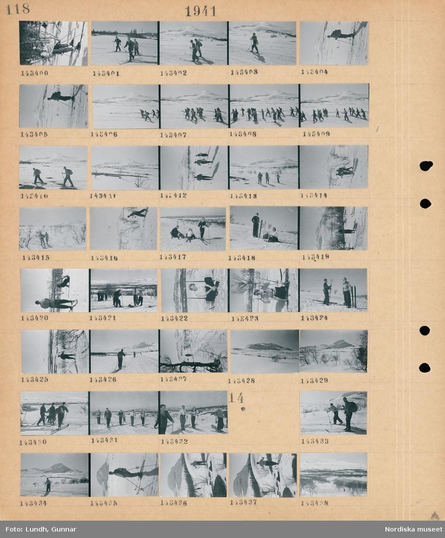 Motiv: (ingen anteckning) ; Kvinnor och män åker skidor i ett snötäckt landskap med fjäll i bakgrunden.   Motiv: (ingen anteckning) ; Kvinnor och män åker skidor i ett snötäckt landskap med fjäll i bakgrunden.