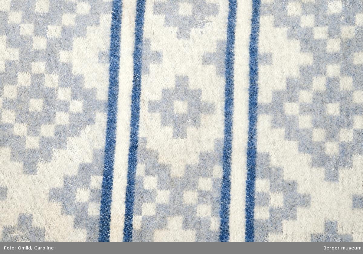 Teppeprøve med ruter utviklet fra korsmønster, med bord i liknende mønster innrammet av to mørkere striper.