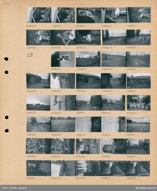 """Motiv: (ingen anteckning) ; Två kvinnor varav en med folkdräkt sitter på en veranda, en man kardar ull och en kvinna står bredvid, en kvinna leder en ko på en väg och ett barn cyklar.  Motiv: (ingen anteckning) ; En kvinna med en cykel med packning, en fågelskrämma står i en odling, landskapsvy med åkrar och skog, en bäck, exteriör av ett hus, en kvinna med en cykel, en gårdsmiljö med timmrade hus, en vägskylt """"Rättvik Leksand Falun"""", rök från en byggnad, bikupor, en person cyklar på en väg, en äng, en midsommarstång, landskapsvy med åkrar och höhässjor, en björk, ett solur, porträtt av en kvinna, exteriör av ett timmrat hus, en kvinna i folkdräkt ställer träkärl till torkning."""