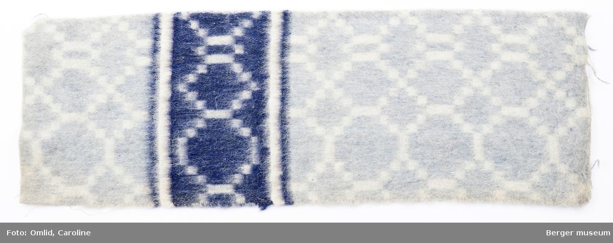 En prøve. Teppe med gjentagende rutemønster som blir brutt av samme mønsterbord i en annen farge. Inverterte mønsterfarger på baksiden.