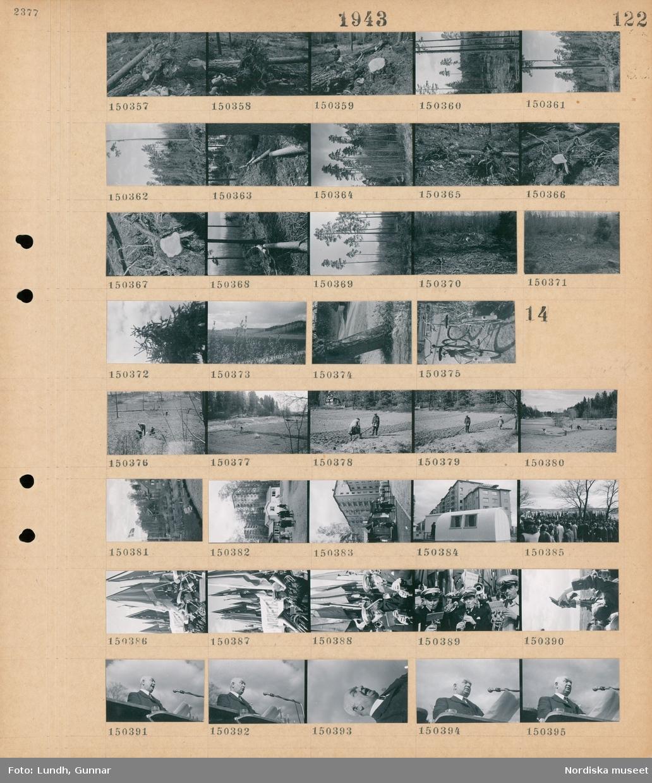Motiv: (ingen anteckning) ; En rotvälta, träd i skogen, trädstammar som ligger på rad i skogen, parkerade cyklar.  Motiv: (ingen anteckning) ; En kvinna och en man arbetar på en åker, exteriör av hus, människor vid små stugor som troligen är en utställning med hyreshus i bakgrunden, troligen första maj demonstration på gärdet, ett demonstrationståg med fanor och banderoller, en blåsorkester spelar, en man med kamera, statsminister Per Albin Hansson talar.