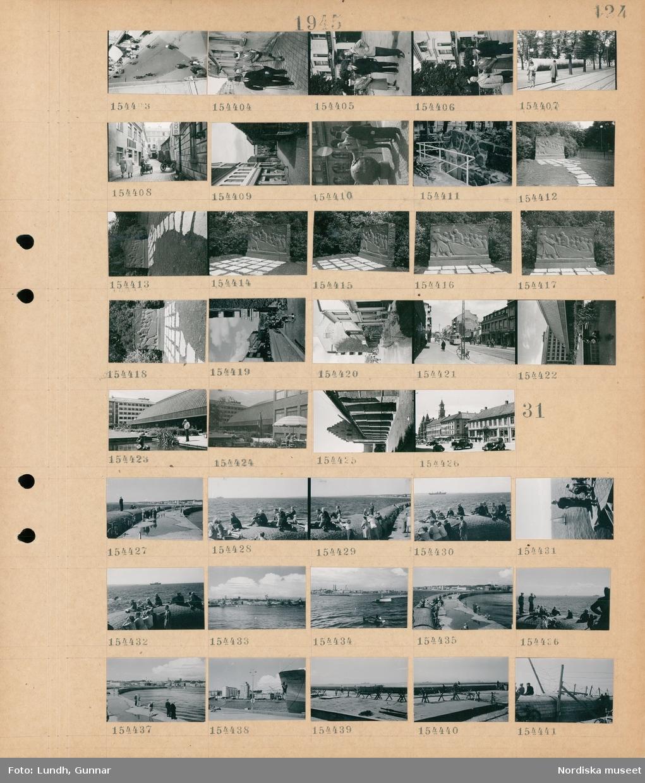Motiv: (ingen anteckning) ; Stadsvy med fotgängare och cyklister, porträtt av två män varav en är fotograf Gunnar Lundh och en kvinna, två män står vid en sjömina, ett konstverk, stadsvy med fotgängare och spårvagn, exteriör av byggnad.  Motiv: (ingen anteckning) ; Människor promenerar och sitter på en pir, stadsvy med vatten och bebyggelse, taggtrådshinder på en pir.