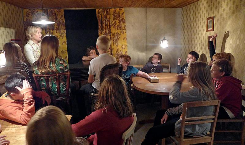 Ei gruppe barn og en voksen inne i utstillinga Sally Jones, de sitter rundt tre bord.