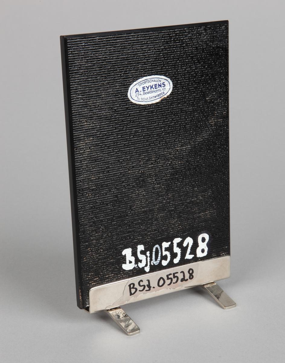 Plakett gitt til LYRA i 1951. Abigail Spencerakett på sort stein med rundt merke samt skilt med tekst.