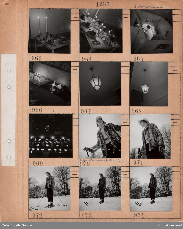 Motiv: Stockholm, mindre bord med julprydnader, två höga tända ljus, pepparkakor, monter i form av ett rum med barndockor i sängar, lampa i form av John Blund med sitt paraply, julprydnader, ljusstakar med tända ljus, taklampa, servering ovanifrån runda bord med vita dukar, kvinna, Elsa Persson född Lundh, klädd i sportkläder och kort jacka av fläckigt kattskinn, åker skidor i snöigt landskap.