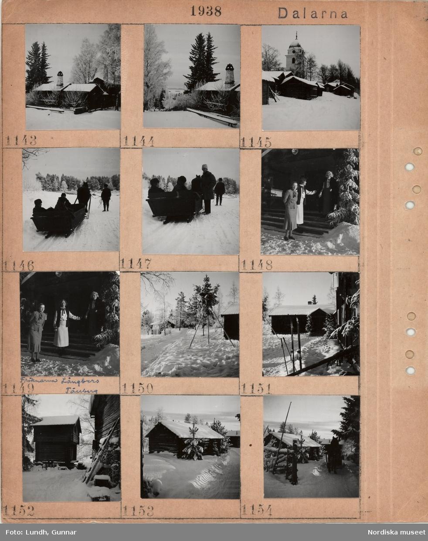 Motiv: Dalarna, timmerbyggnader i snö, höga träd, kyrktorn, släde med passagerare dragen av en häst på snöig väg, tre kvinnor, fröknarna Långbers Tällberg, på yttertrappa i snö, ett par skidor och stavar nerstuckna i snö, loftbod, gärdesgård.