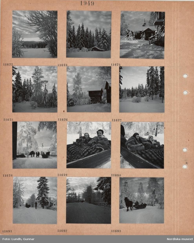 Motiv: Snöigt landskap med öppet fält framfö skog, liten timmerbyggnad framför snöiga granar, gårdsplan i snö med tre avkvistade granstammar med toppruskor ställda i trekant, yttertrappa med träräcke, snöiga träd, timmerhärbre, hästdragna slädar, en flicka och en kvinna i päls nerbäddade i en släde under fälltäcke, släde på snöig väg, trägärdsgård.