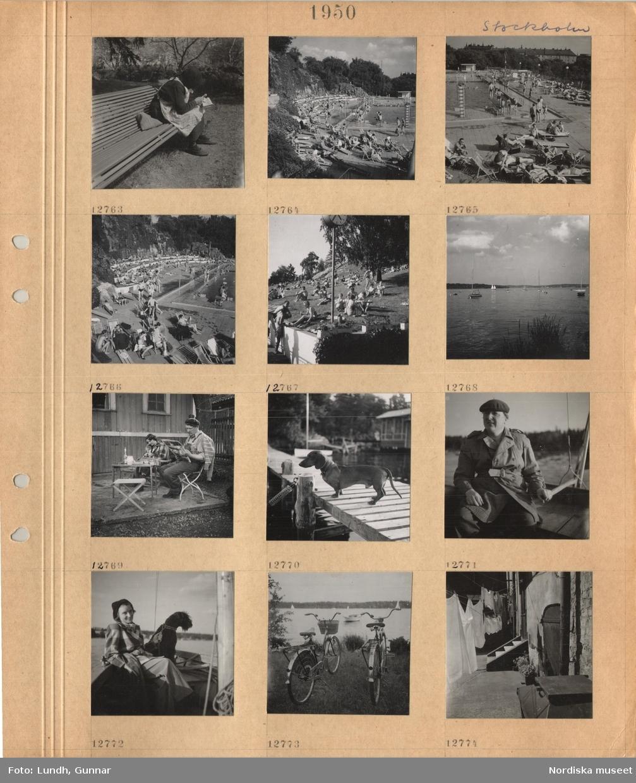 Motiv: Stockholm, äldre kvinna sitter på parkbänk och läser tidning med förstoringsglas, utomhusbad med bassäng, badande, solande personer i baddräkt i solstolar och på grönytor, sjö med segelbåtar, kvinna som handarbetar och man som läser tidningen sitter i trädgårdsmöbler framför trähus, glas och flaska på bordet, en tax med halsband står på en brygga, man i rock och basker sitter vid rodret i mindre båt, kvinna i långbyxor, kappa, hatt sitter i fören i mindre båt med en hund i koppel, två cyklar parkerade vid stranden av en sjö, tvätt upphängd på linor på bakgråd, sopkärl.