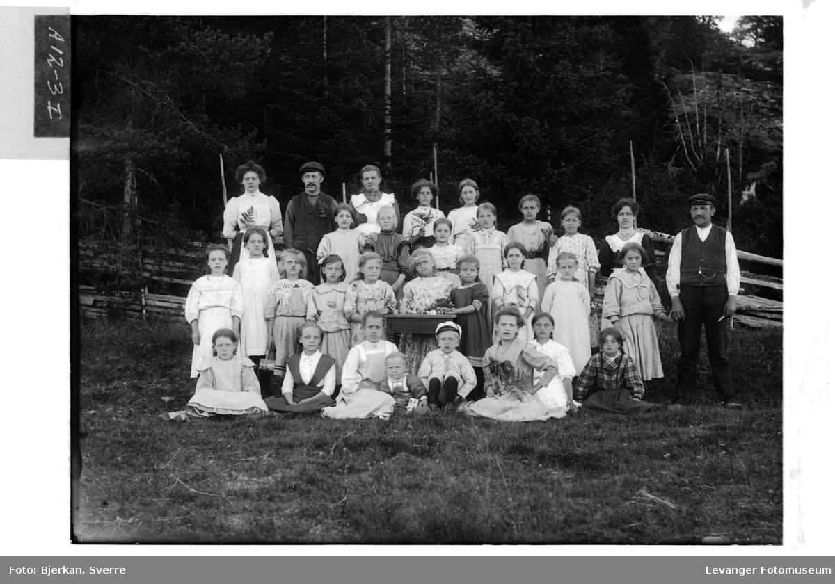 Gruppe barn og voksne fotografert ute med kafferservise, kan være storfamile. men antall barn kan tyde på en annen type gruppe.
