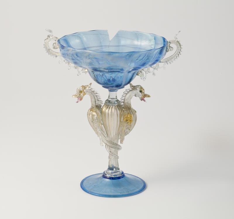 Prydglass med skålformet og vid kupa. Kupaen er blåfarget, mens hankene er utført i klart glass. Stetten er utformet som dragelignende vesener i klart glass med forgylt detaljering. Foten er sirkulær og blåfarget.