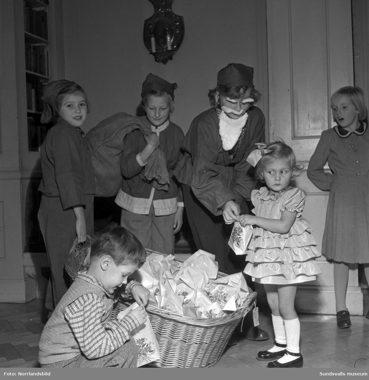 Söndagsskolebarnens julfest på församlingshemmet i Sundsvall. Här pågår utdelning av godispåsar och de tre tomtarna heter Britt Edlund, Lajla Mari Dahlbom och Karin Nilsson. Barnen som just fått sina presenter är Arne Svärd och Monica Glad.