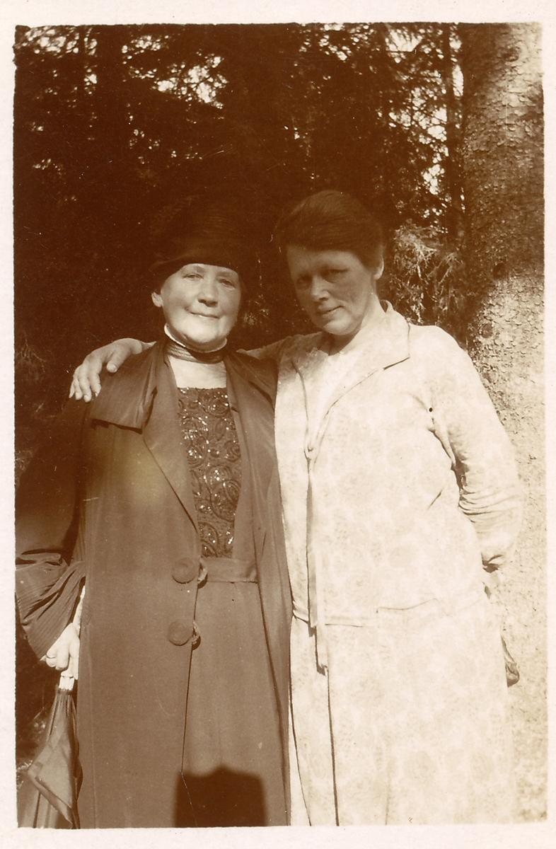 To kvinner fotografert utendørs. Trær i bakgrunnen. Sommer. Fru Hansen og Sigrid.