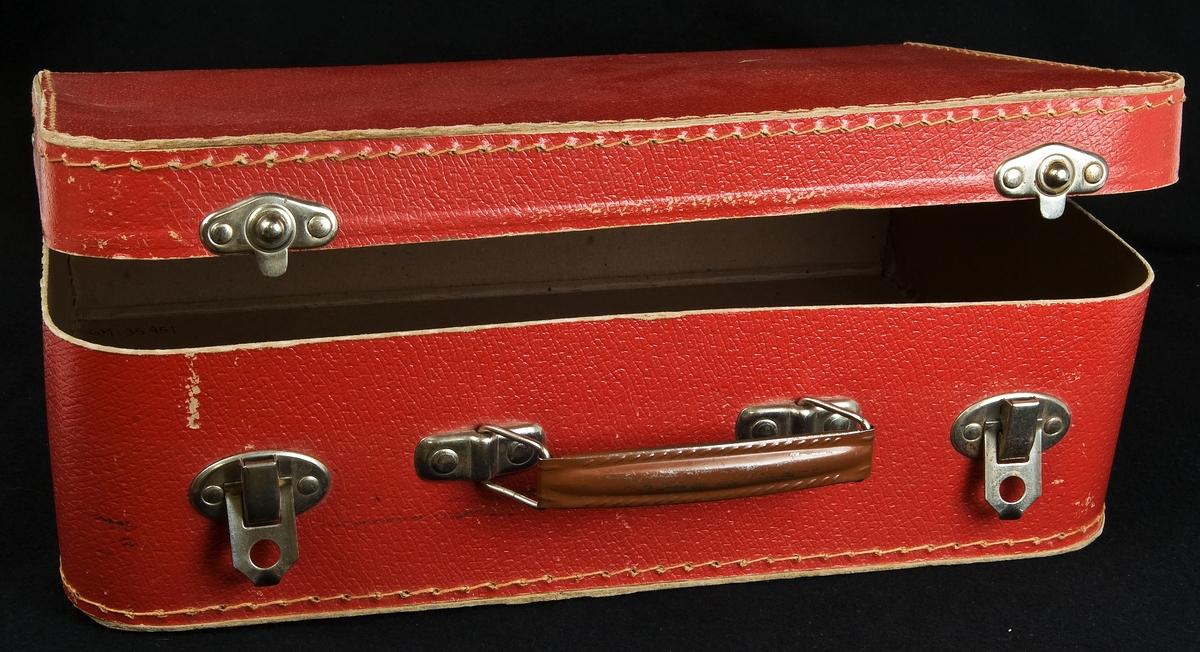 En röd resväska, leksaks-, av pressad papp. Försedd med låsanordning av metall och bärhandtag av brunmålad metall.