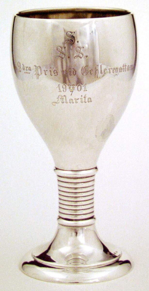 Prispokal av silver på fot. Graverat på framsidan: SSS 2 dra pris vid Gefleregattan 22/7 1901 Marita. Stämplar: CGH, kattfot, stadsstämpel Y6 (1901).
