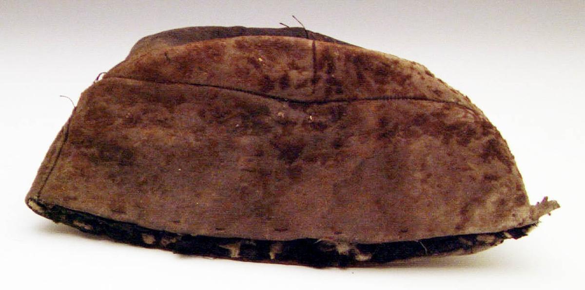 Mansmössa av skinn med rester av brun hårbeklädnad. Mössan är sydd av kilar (med många inkilade skarvar) och fodrad med vadderat, svart bomullstyg fastsytt på pappstomme. Mössan är tillplattad och något trasig. Den ger ett ålderdomligt intryck - tidigt 1800-tal.