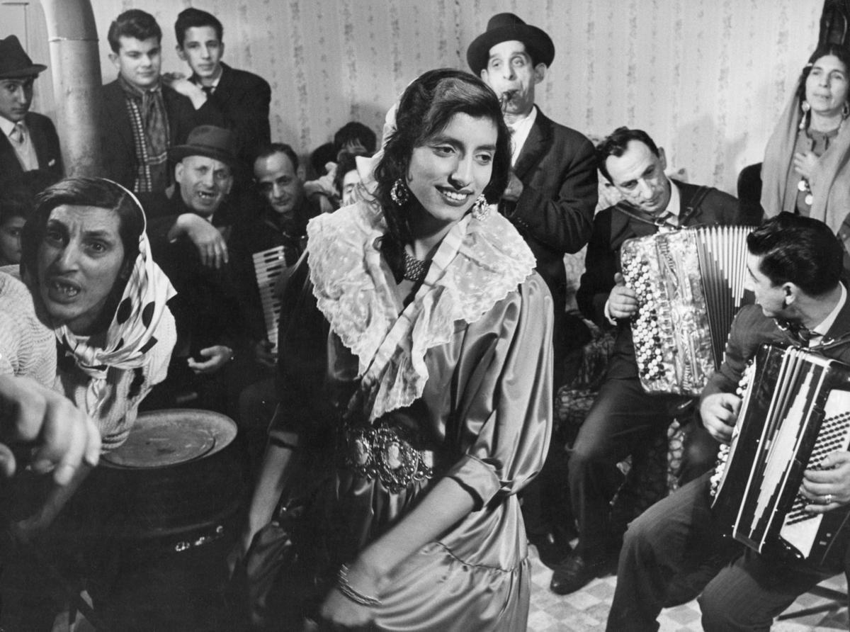 Musikframträdande 1963, taget i samband med inspelningen av Fokus, ett fördjupande nyhetsprogram i SVT som började sändas samma år. Det första avsnittet handlade om Katarina Taikons bok Zigenerska (1963) som då var högaktuell och kom att bli startskottet för debatten om romers rättigheter i Sverige. Bilden är tagen innifrån en bostadsbarack, till vänster syns ett oljefat med skorsten.   Programmet undgick varken publik eller kritik. Uppståndelsen gjorde mannen bakom Fokus, Bo Isaksson, bekymrad. I ett uttalande framförde han sin lättnad över att Lennart Hylands mer lättsamma Karusell-serie började sändas samma dag som det andra programmet av Fokus kom. På det sättet slapp man den obehagliga uppmärksamhet som det första avsnittet hade väckt.