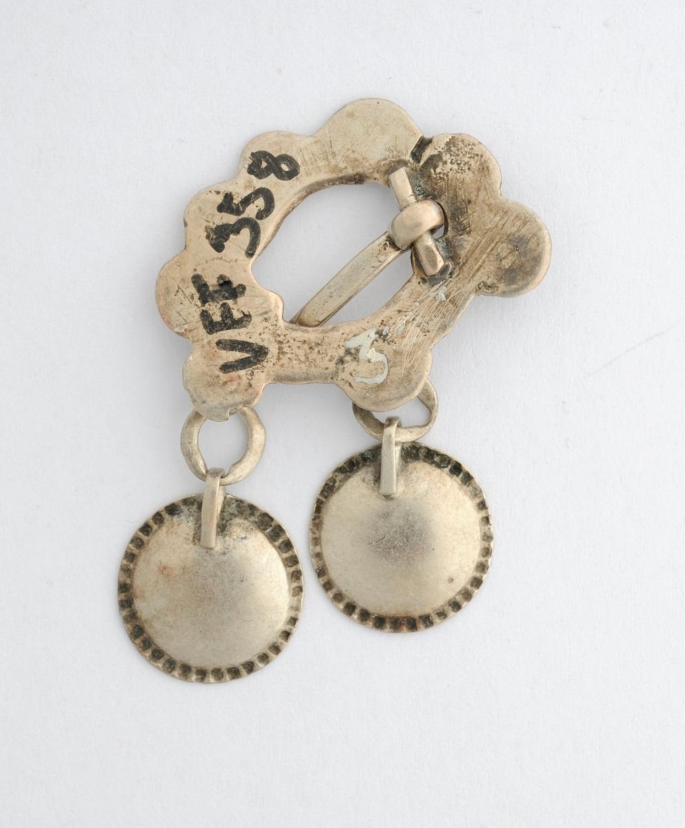 Sølje, sprette med skåler i sølv (ingen stempel). Ovalt forma med avrunda taggar i ytre kant. Tre hemper med ringar. I ringane er det festa skåler (lauv). Ei skål manglar. Glatt på baksida.