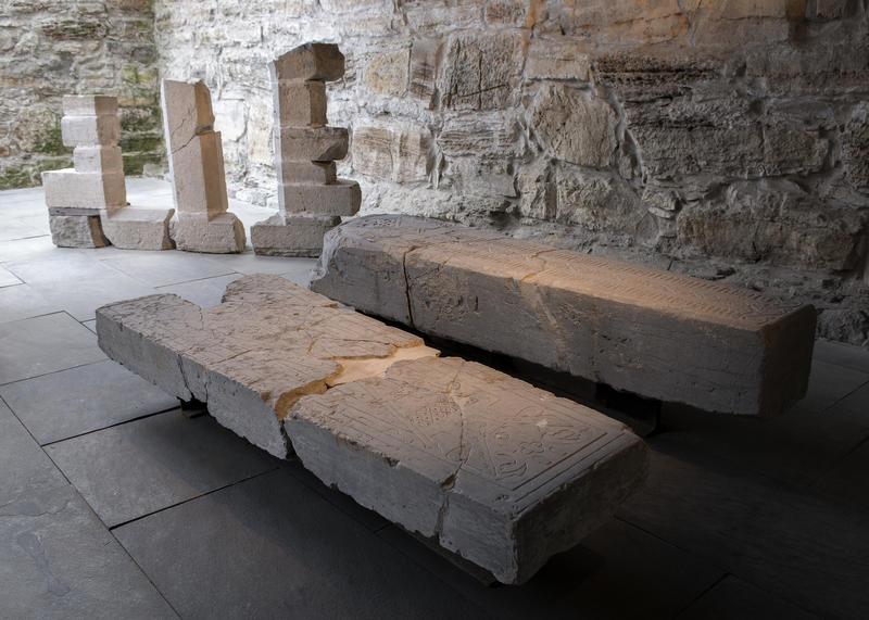 De to biskpgravsteinene der de står utstilt i dag; i Storhamarlåven, sammen med deler av et gotisk vindu.
