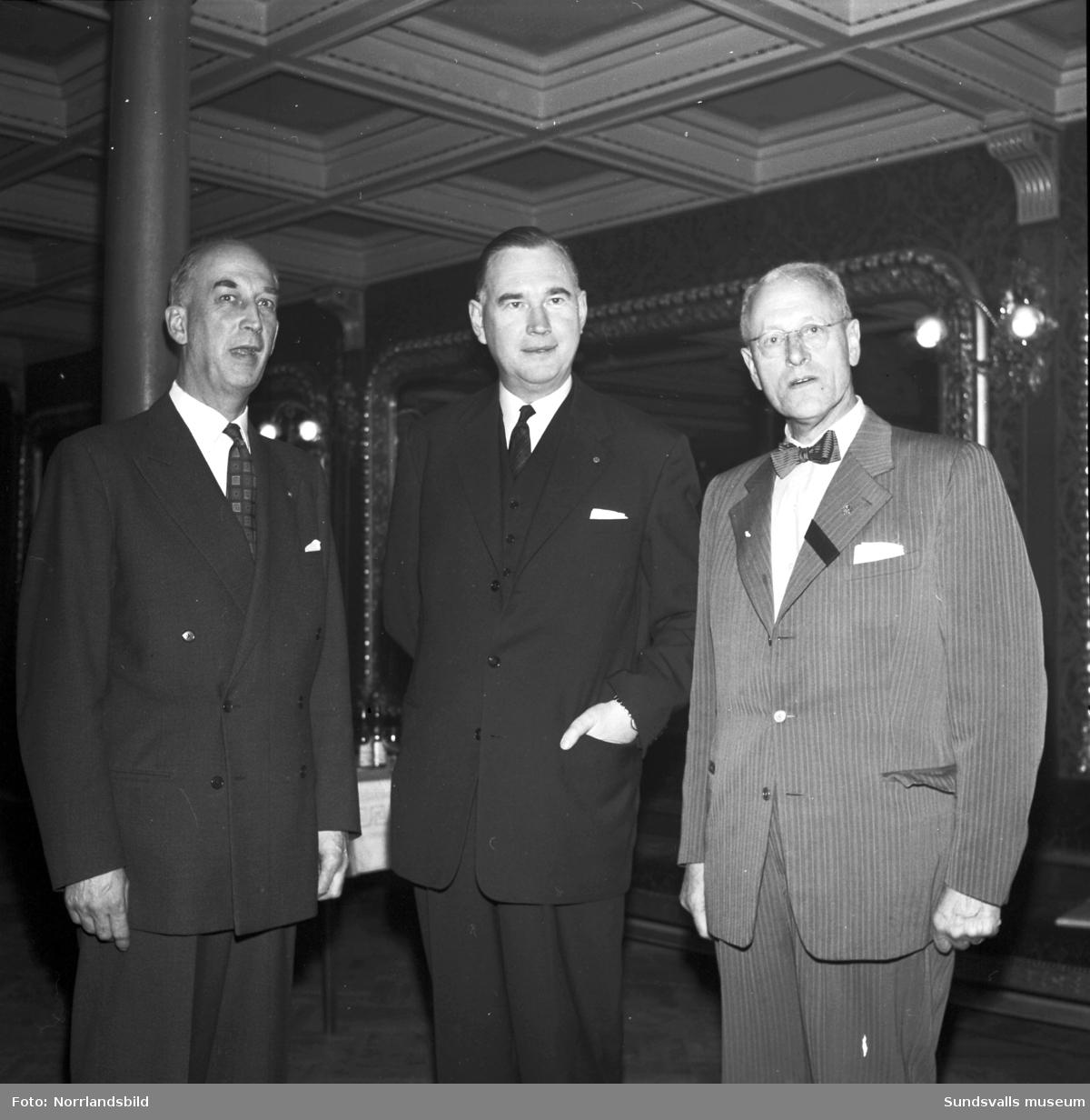 Tre kostymklädda herrar poserar i Stadshusets festvåning.