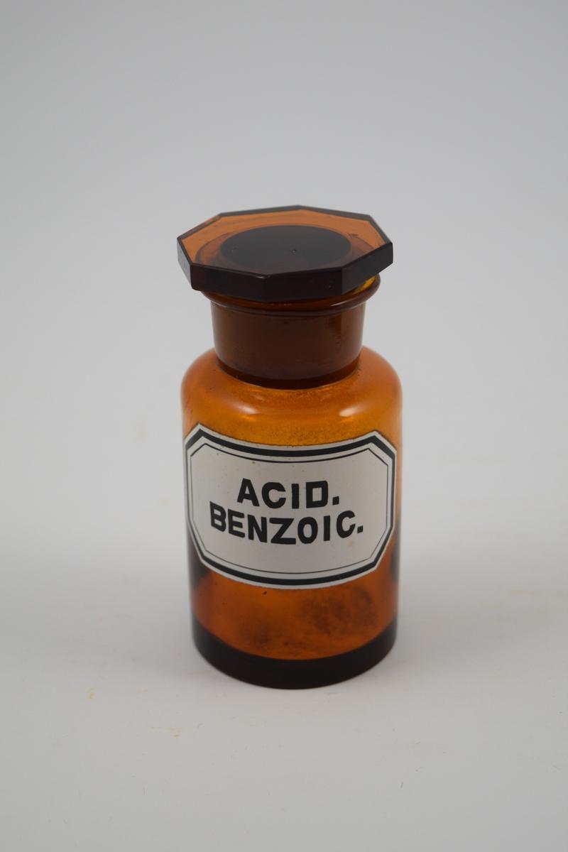 Brun glasskrukke med glasspropp. Hvit etikett med sort skrift. Acid Benzoic ble brukt som konserveringsmiddel til salver og øyedråper med mer. Også brukt til syltetøy.