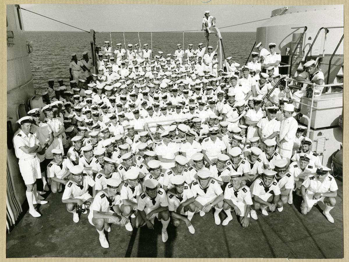 Bilden föreställer ett grupporträtt där hela besättningen av minfartyget Älvsnabben är samlad på akterskeppet under långresan 1966-1967.