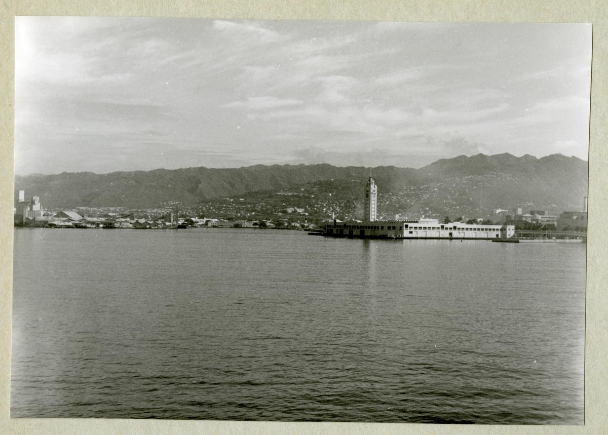 Bilden föreställer ett berglandskap. Längs med kustlinjen syns bebyggelse. Bilden är tagen under minfartyget Älvsnabbens långresa 1966-1967.